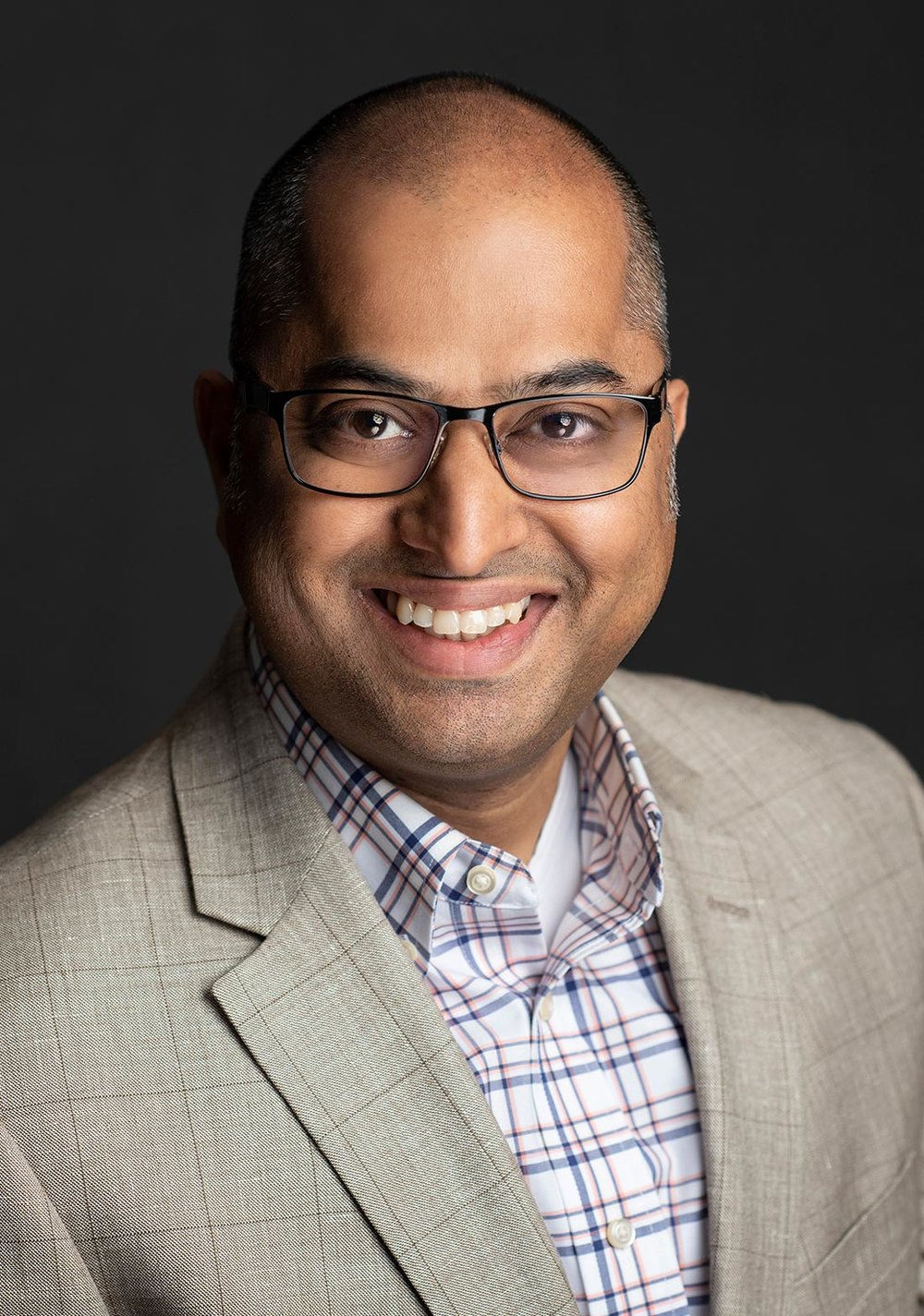 Professional headhshot of man with glasses and jacket