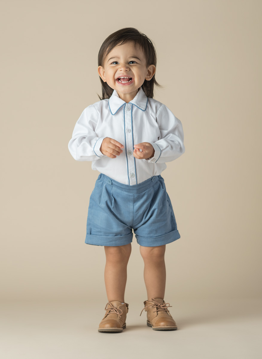 Portrait of a toddler wearing a white button up with blue shorts