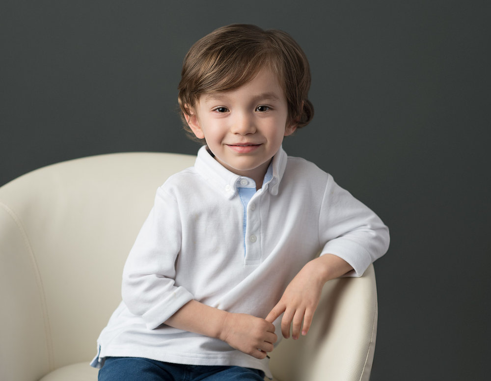 Studio portrait of young boy in white shirt on grey background