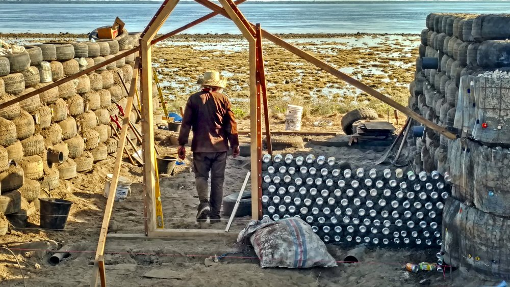 -      It takes One`s vision and dedication to make it work...    Here: Michael Reynolds entering his envisioned tropical     Earthship design that we collectively brought to reality