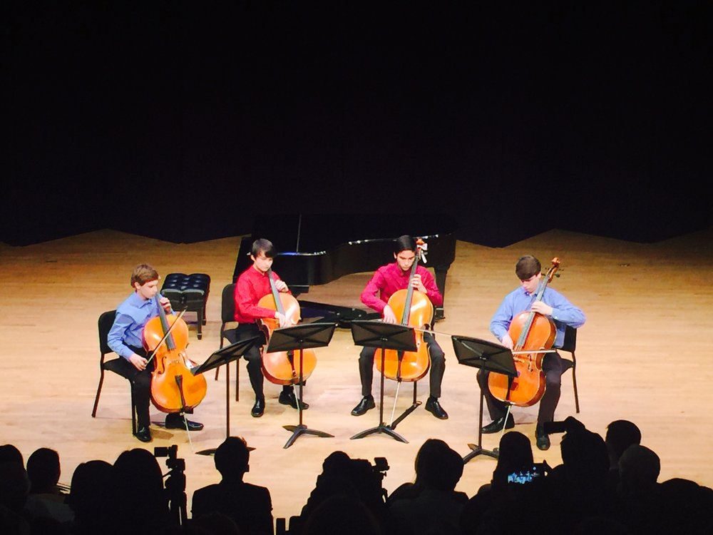 A cello quartet (l-r: Evan Nicholson, Mingdao Gavalda, Jordan Leslie and Will Goodwin) perform on the December 2016 concert.