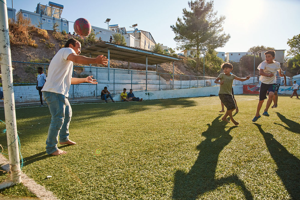 A game of football between young and old. Vial Refugee Camp, Chios, Greece.