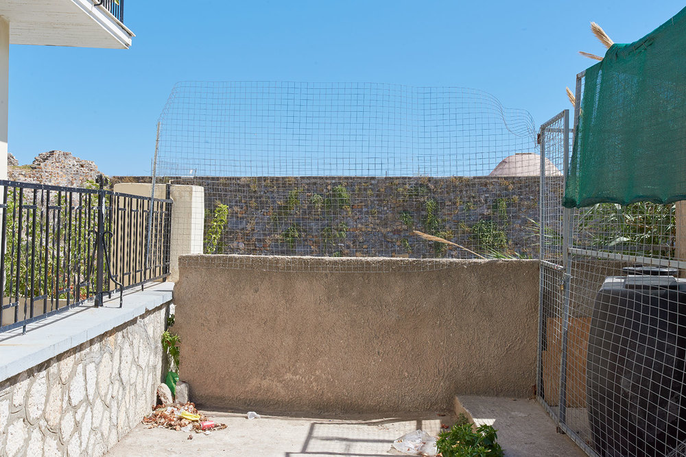 The Souda Camp has come under attack from members of the far-right group, Golden Dawn. This wall stands on top of a slope, overlooking part of the camp. The fence was erected to prevent further instances of Golden Dawn members throwing boulders down on the tents below.
