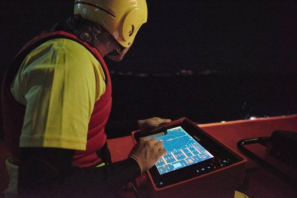 Proactiva, the Spanish boat rescue organisation has a team of first-responders based in Skala, Lesvos. Here, a crew member looks into the darkness during a late night search and rescue simulation exercise at sea. Charities Lighthouse Relief and Refugee for Refugees joined Proactiva in the exercise.