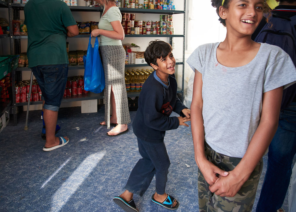 Kids mess about while a volunteer assists a man with his selection of food items. House of Humanity, Lesvos, Greece.