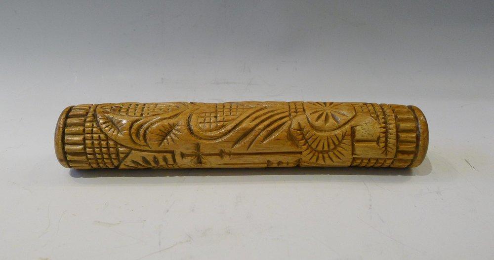 5.Rouleau sculpté en creux d'un grand ostensoir cerné par un bandeau de stries à son sommet et reposant sur une rosace à 4 pétales inscrites dans un carré.2 croix entourent l'ostensoir.A l'opposé une rosace à multiples branches, un coeur et une fleur.Initiales T.G., bois de charme, Haute-Loire, L : 22,5 cm.