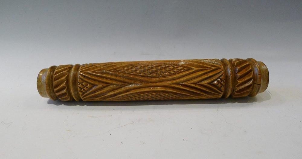 11.Rouleau sculpté en creux de 4 motifs en forme de losanges garnis de quadrillages et de striures.L : 28 cm.