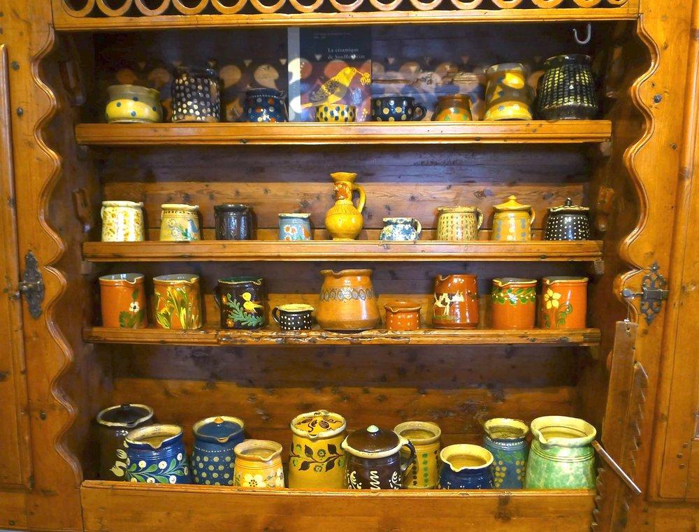 Le magnifique vaisselier du Queyras rempli de poteries.