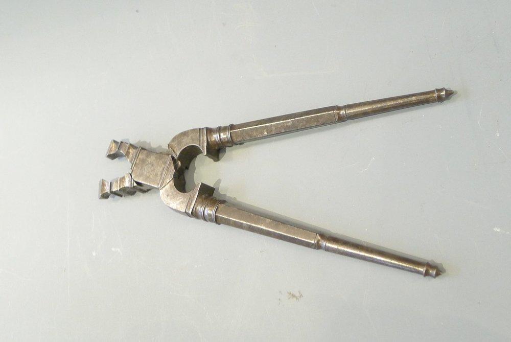 21.Casse noisettes et pignons en fer forgé, vraisemblablement réalisé par un armurier, 17ème.H: 14,5cm .(II.8)