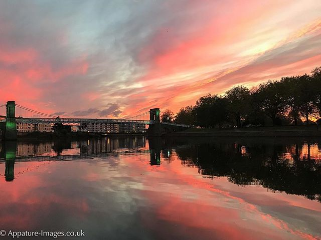 Red and grey sky at sunset on the River Trent looking towards the Wilford Suspension Bridge.