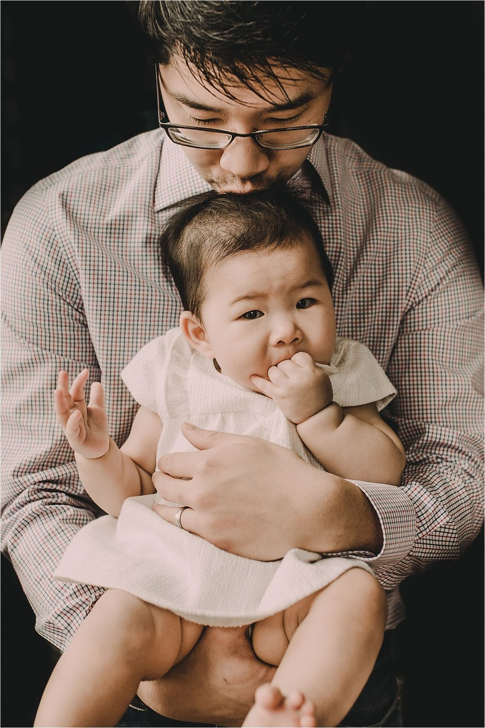 nyc family and newborn photographer dad holds baby girl and dad kisses her head