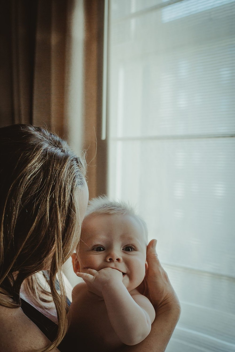 nyc newborn and family photographer mom holding baby with hand in mouth