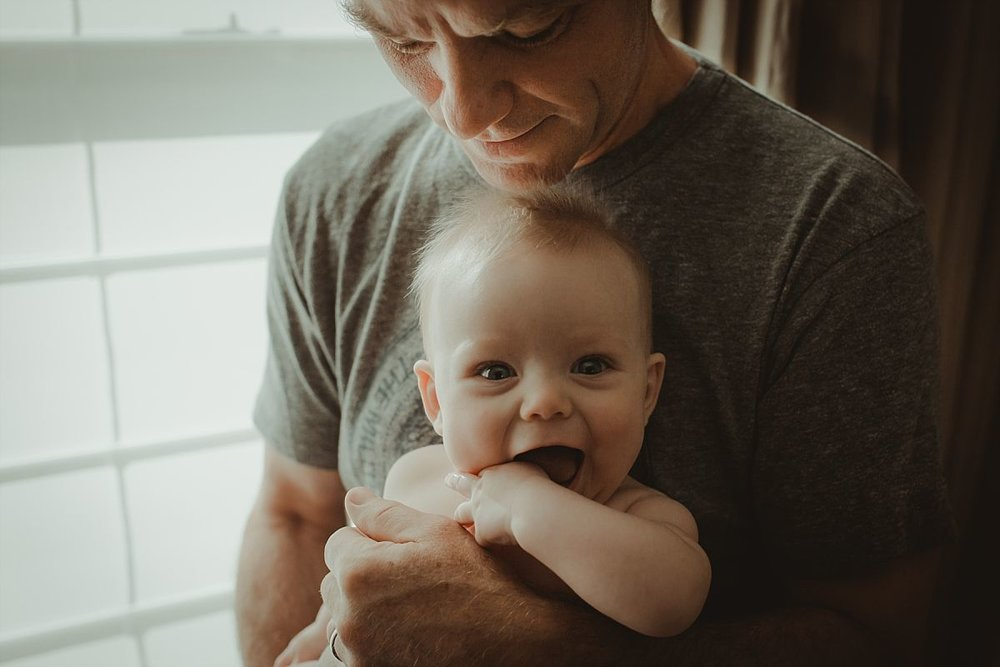 nyc newborn and family photographer dad holding baby with hand in mouth