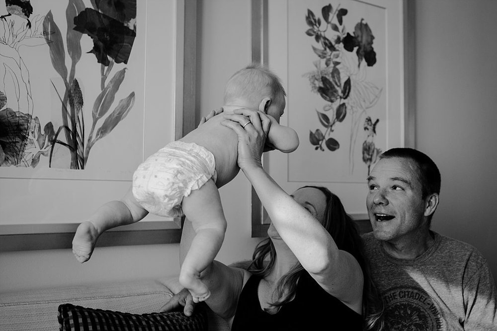 nyc newborn and family photographer dad and mom on couch and baby in air