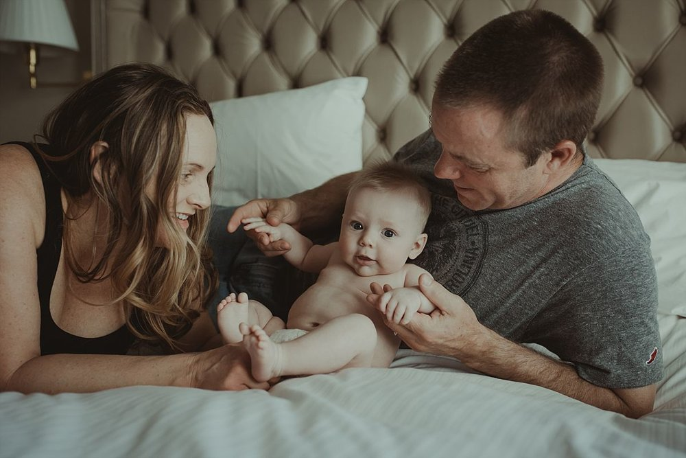 nyc newborn and family photographer mom, dad and baby having fun on hotel bed