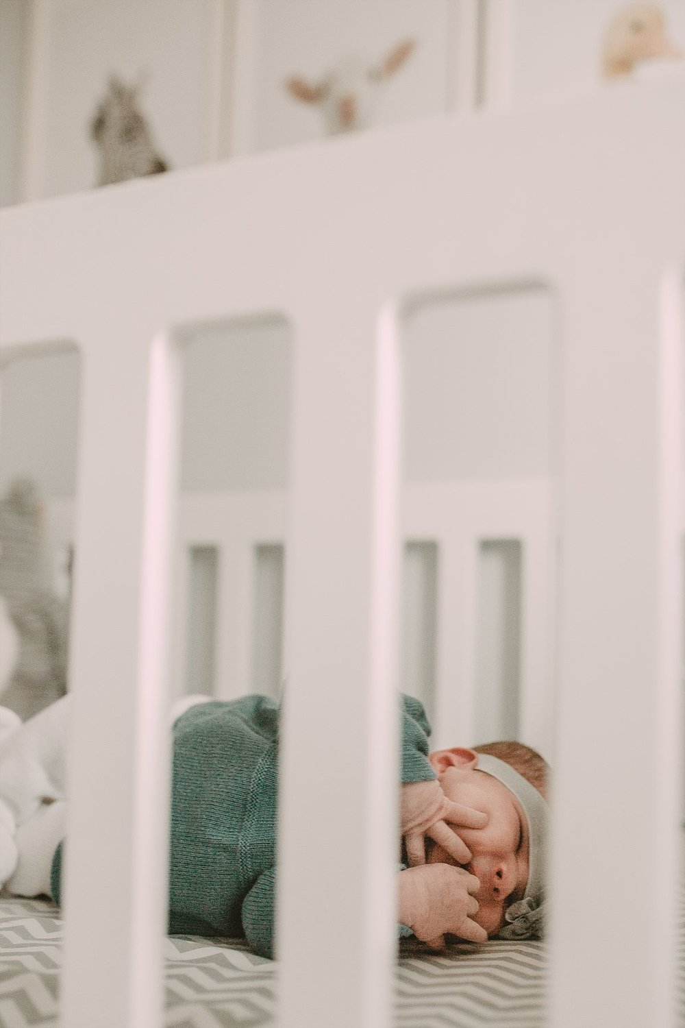 nyc family and newborn photographer newborn in crib in wool outfit with hands in mouth
