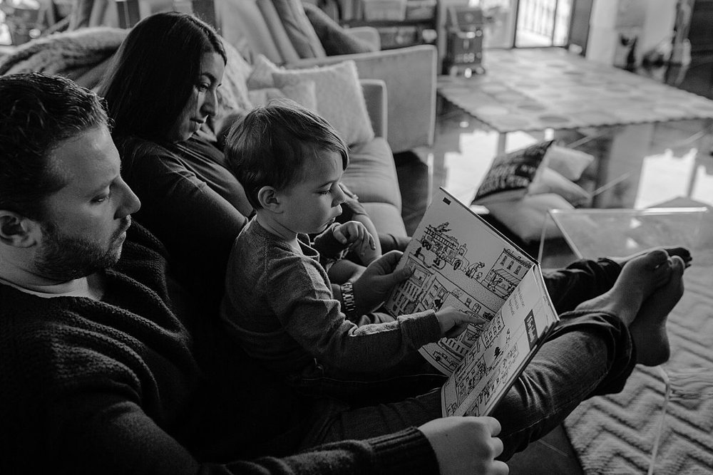 nyc family and newborn photographer family of four reads book together on couch