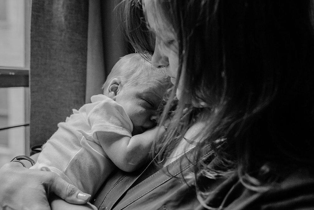 nyc family and newborn photographer Israeli mom holds sleeping newborn boy near window