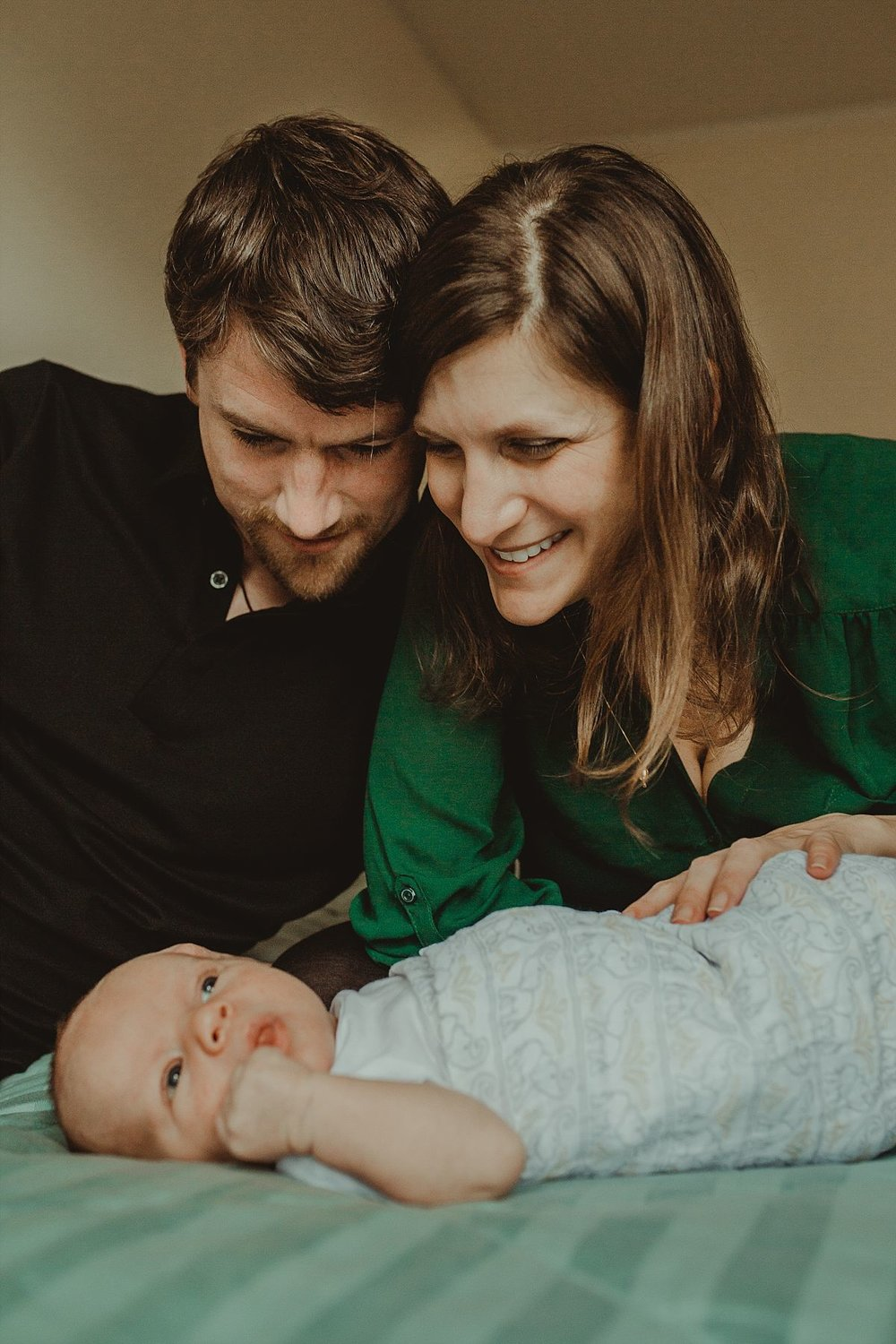 nyc family and newborn photographer mom and and dad look adoringly at newborn son on bed