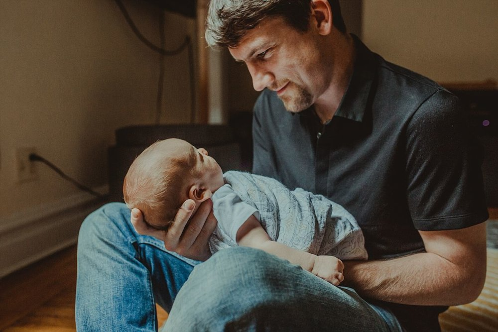 nyc family and newborn photographer dad holds newborn son and looks lovingly at his son