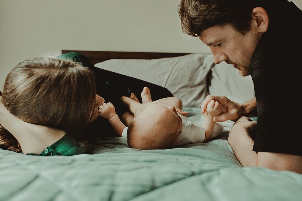 nyc family and newborn photographer mom and dad lie with son on bed playing with his tiny hands