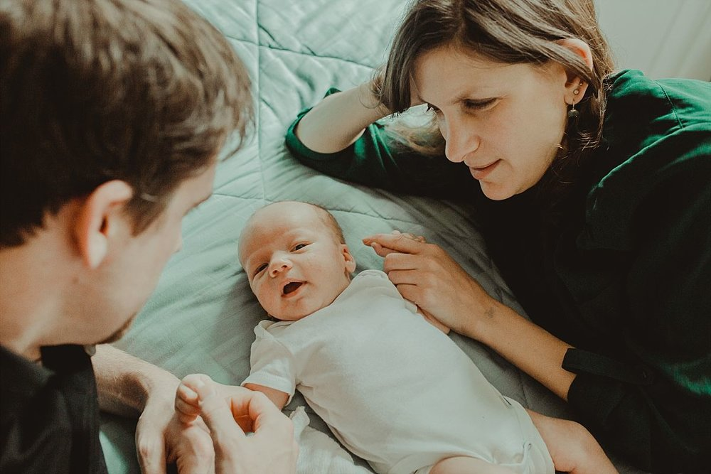 nyc family and newborn photographer mom and dad lie with son on bed playing with him