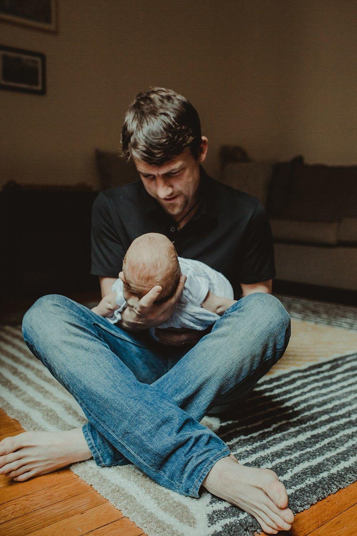 nyc family and newborn photographer dad cuddles newborn son near light filled window