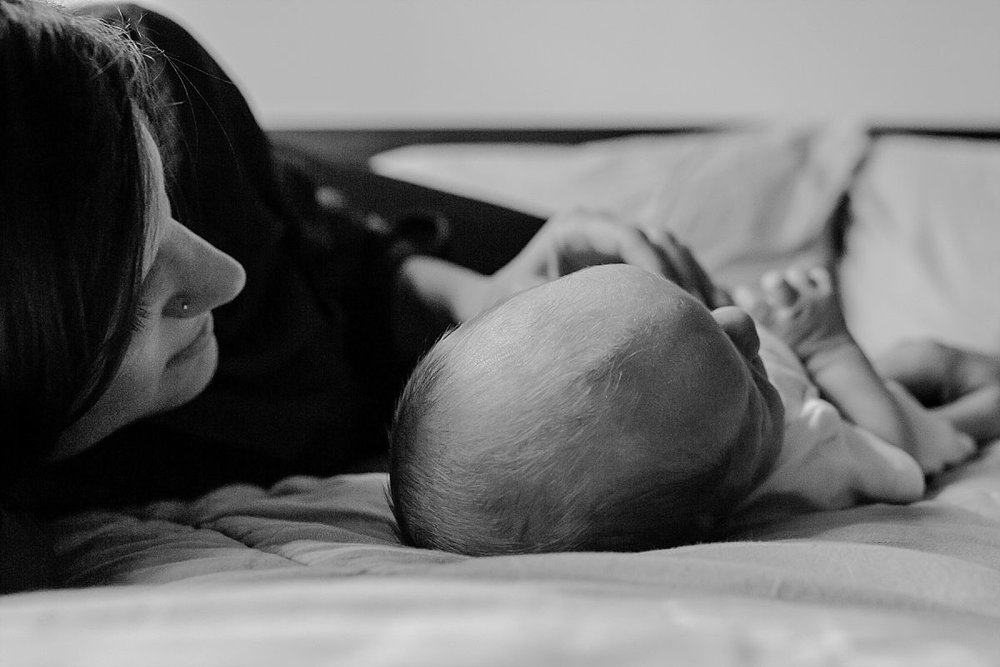 nyc family and newborn photographer mom lies next to newborn on bed