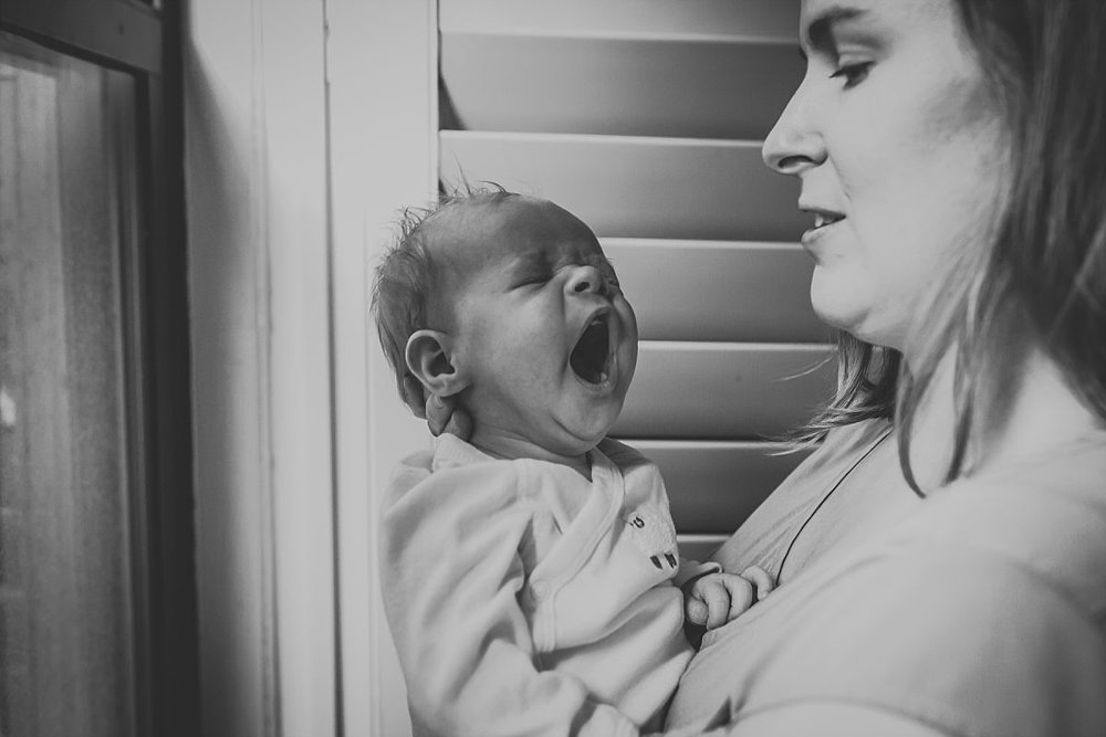 nyc family and newborn photographer mom holds yawning baby girl in apartment by window
