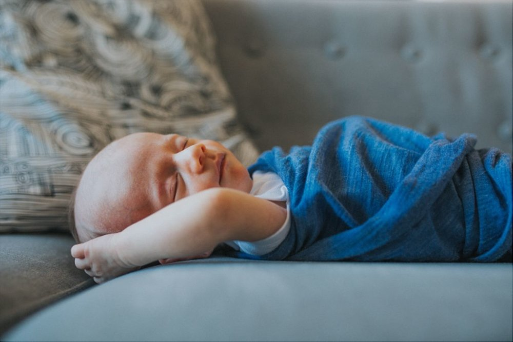 nyc family and newborn photographer newborn son sleeps on couch of upper west side apartment