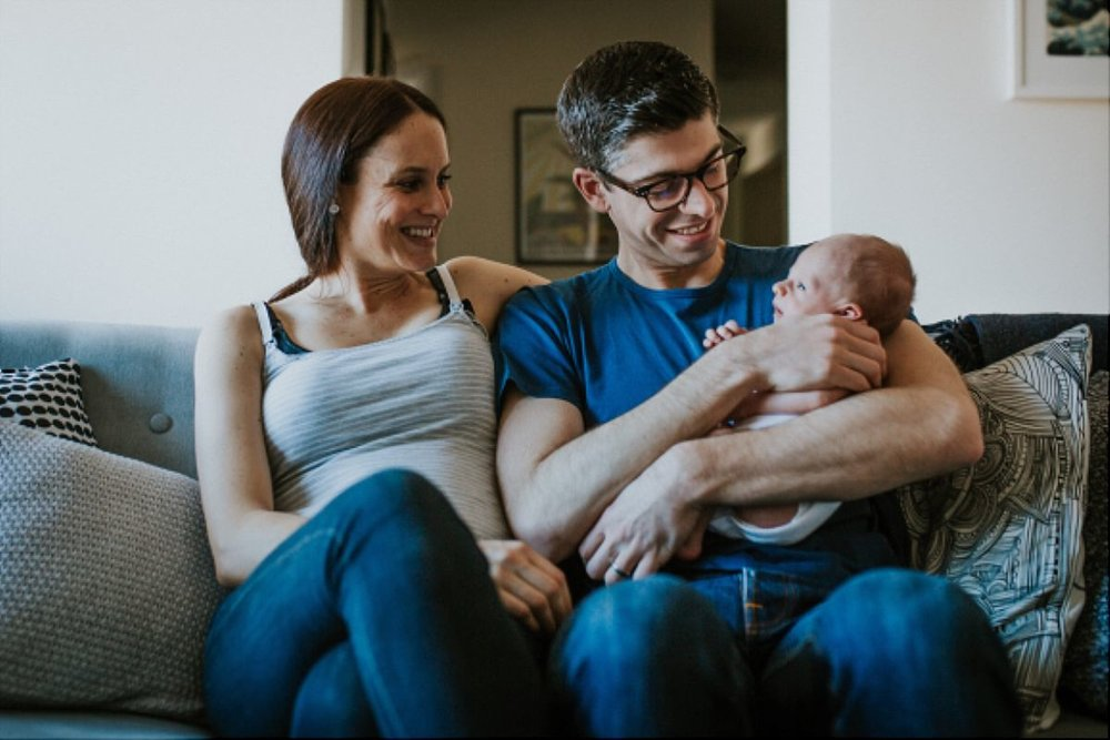 nyc family and newborn photographer mom, dad and newborn son on couch in living room