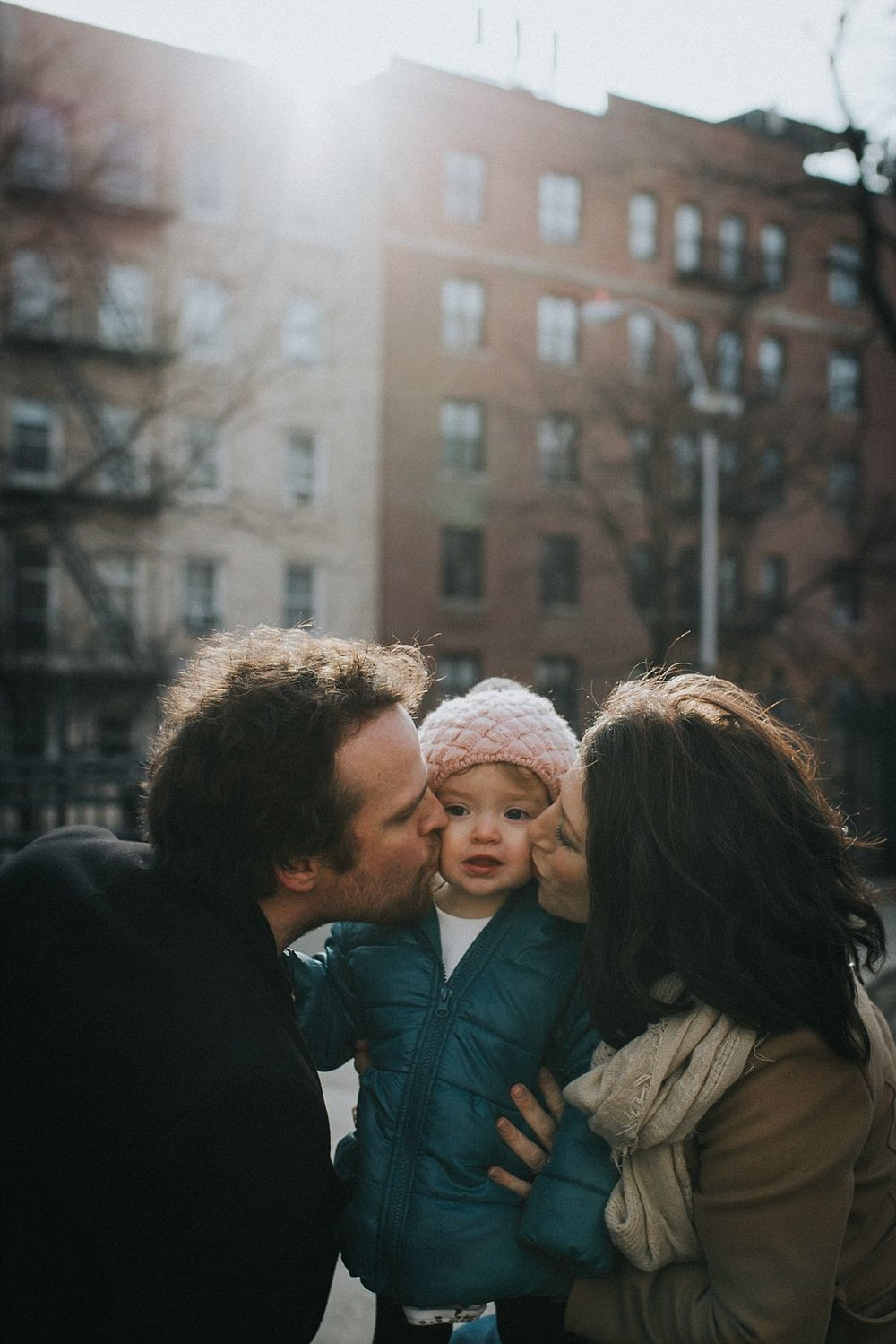 nyc family and newborn photographer, mom and dad sitting on nyc park bench and give toddler daughter big kiss