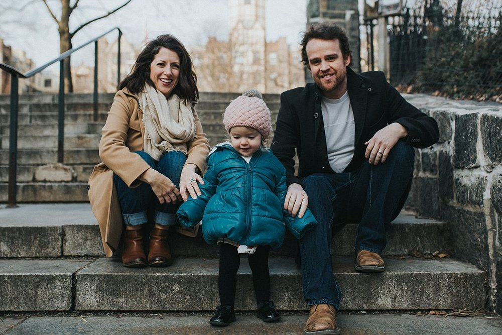 nyc family and newborn photographer mom, dad and toddler sit on steps on nyc park entrance looking at camera