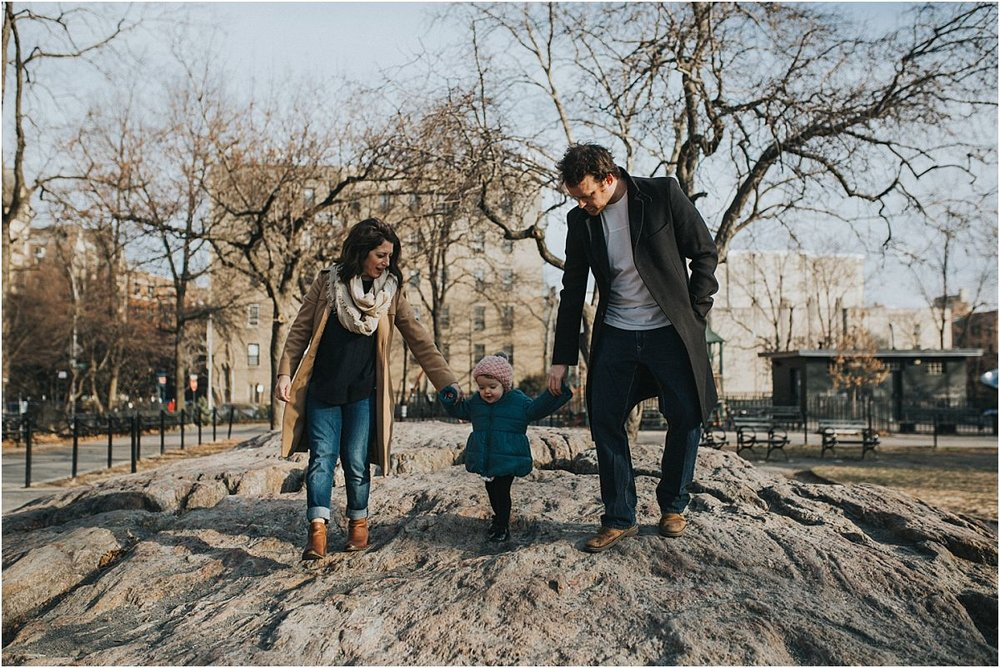 nyc family and newborn photographer mom, dad and daughter climbing on rock in local nyc park bench