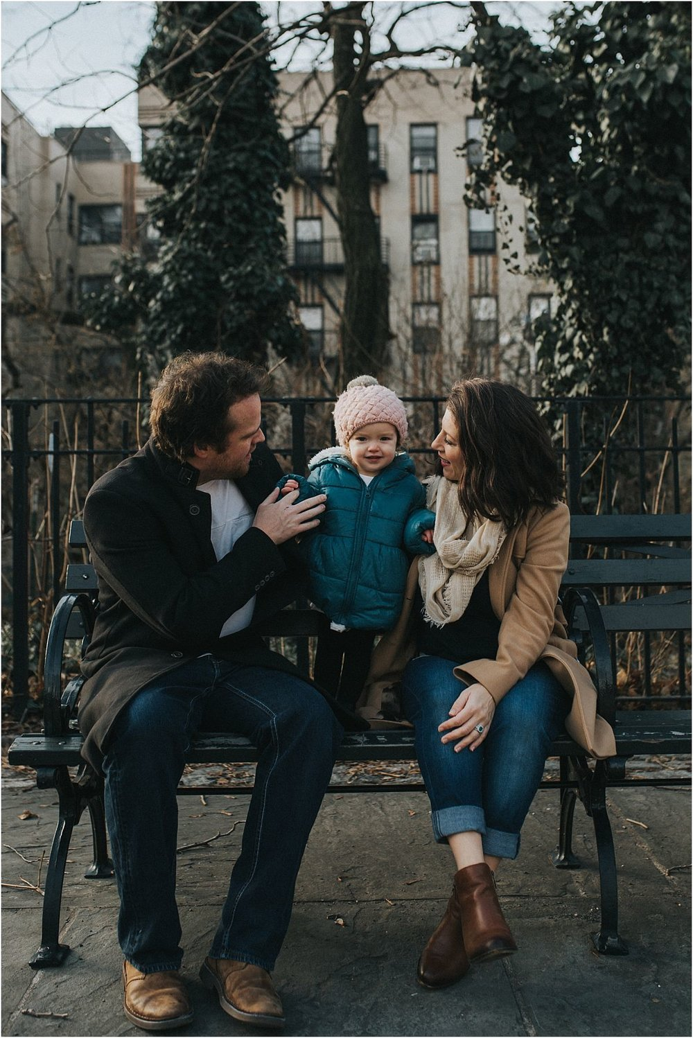 nyc family and newborn photographer family enjoying a moment sitting on nyc park bench on the upper west side