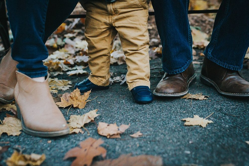 nyc family and newborn photographer mom, dad and toddler feet among fall leaves for outdoor family lifestyle session