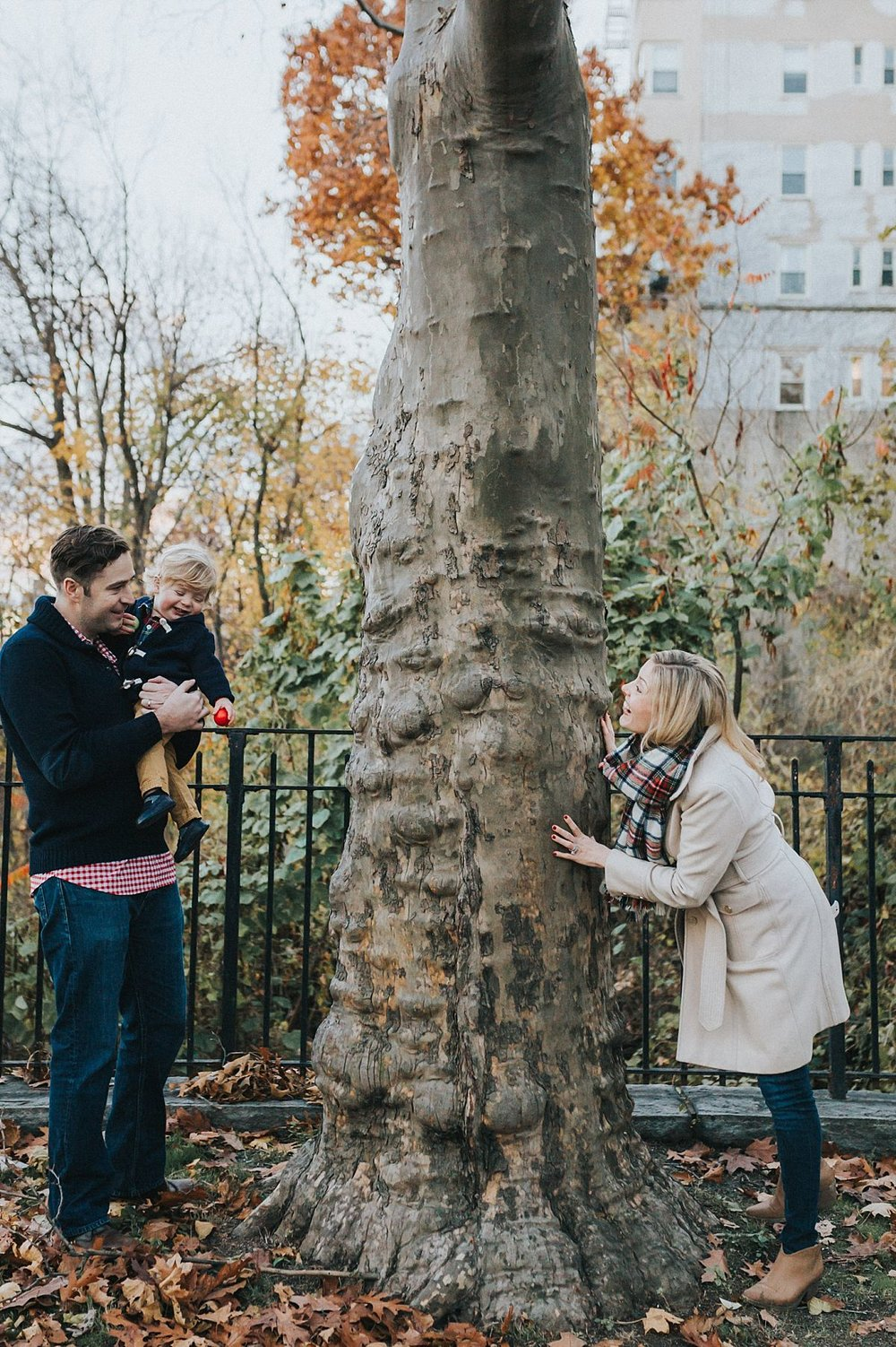 nyc family and newborn photographer mom, dad and toddler boy play peek-a-boo in nyc park for outdoor documentary family session