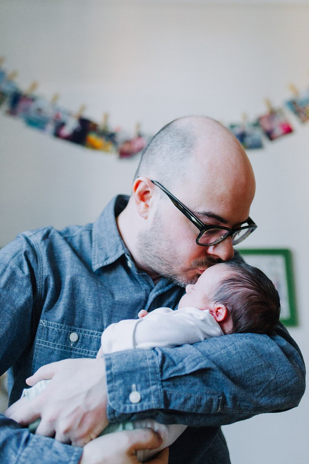 nyc family and newborn photographer dad holds newborn girl and kisses her gently on forehead