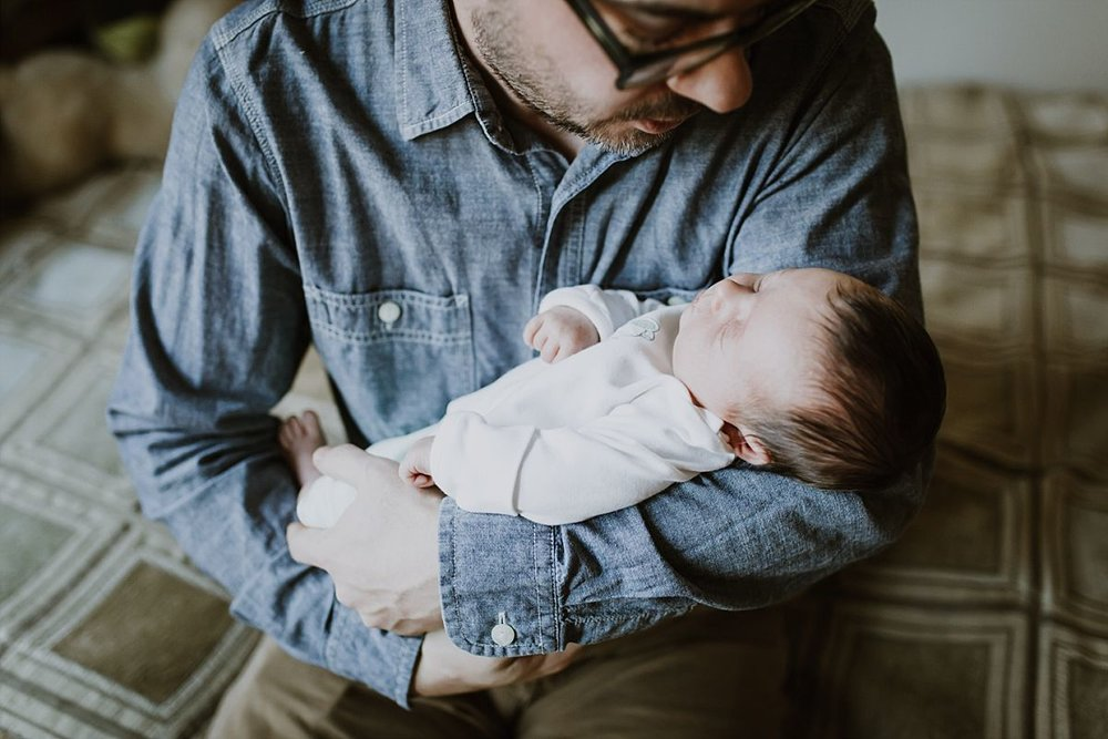 nyc family and newborn photographer dad holds newborn girl while sitting on bed