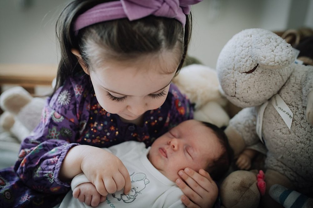 nyc family and newborn photographer big sister holds newborn sister while sitting on bed with stuffed animals