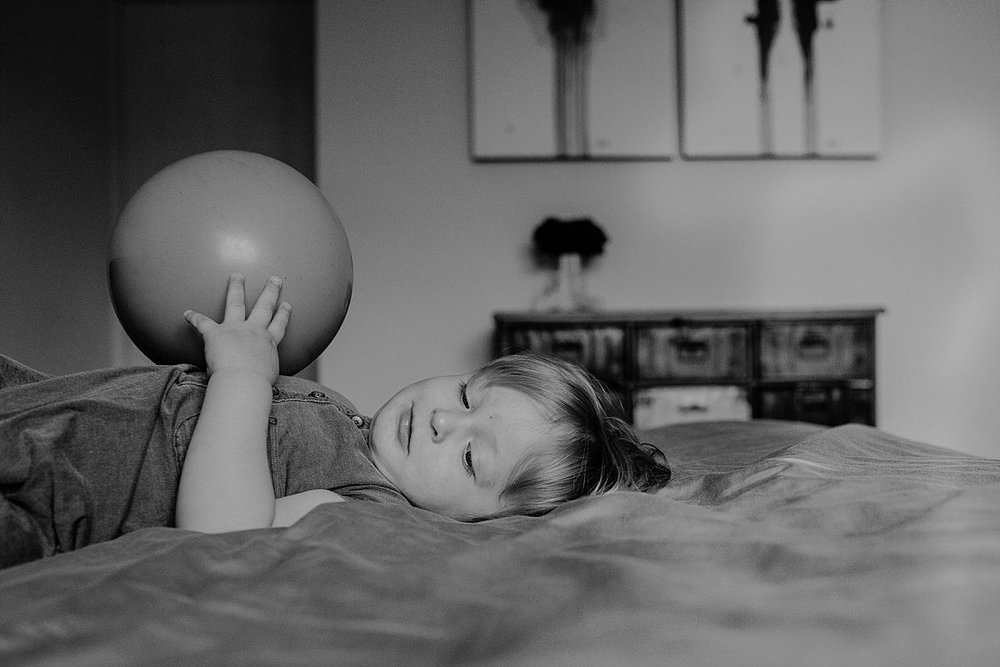 nyc family and newborn photographer son plays with big ball while laying on parents bed in fun nyc family session