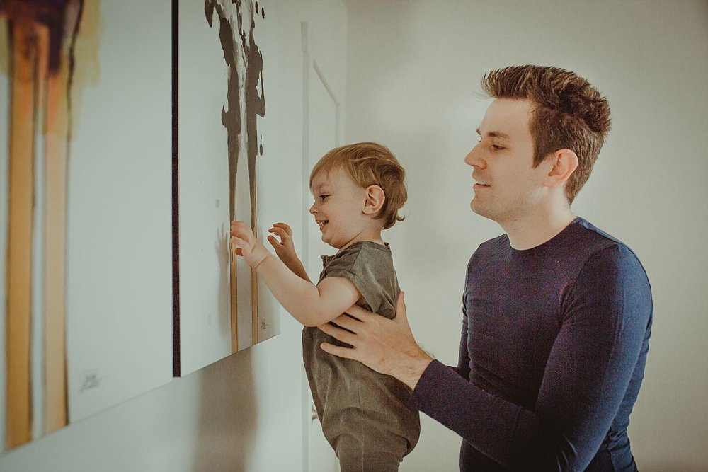 nyc family and newborn photographer son plays with wall hanging while dad makes sure he balances on chester drawers