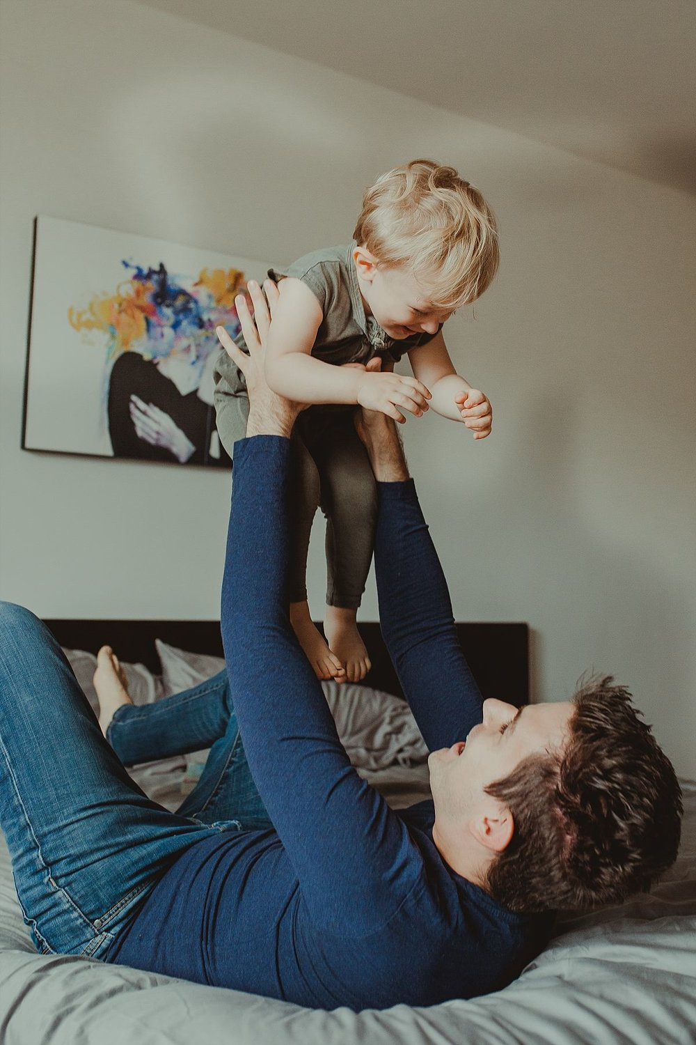 nyc family and newborn photographer father throws giggling son in the air while on bed