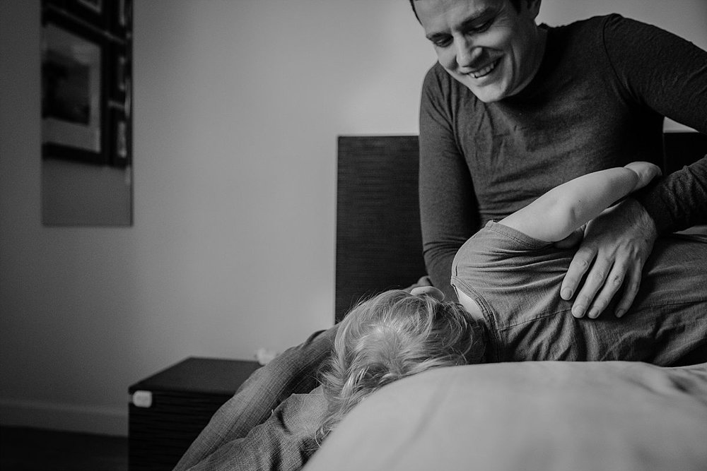 nyc family and newborn photographer dad tickles son for big laughter in nyc in home session