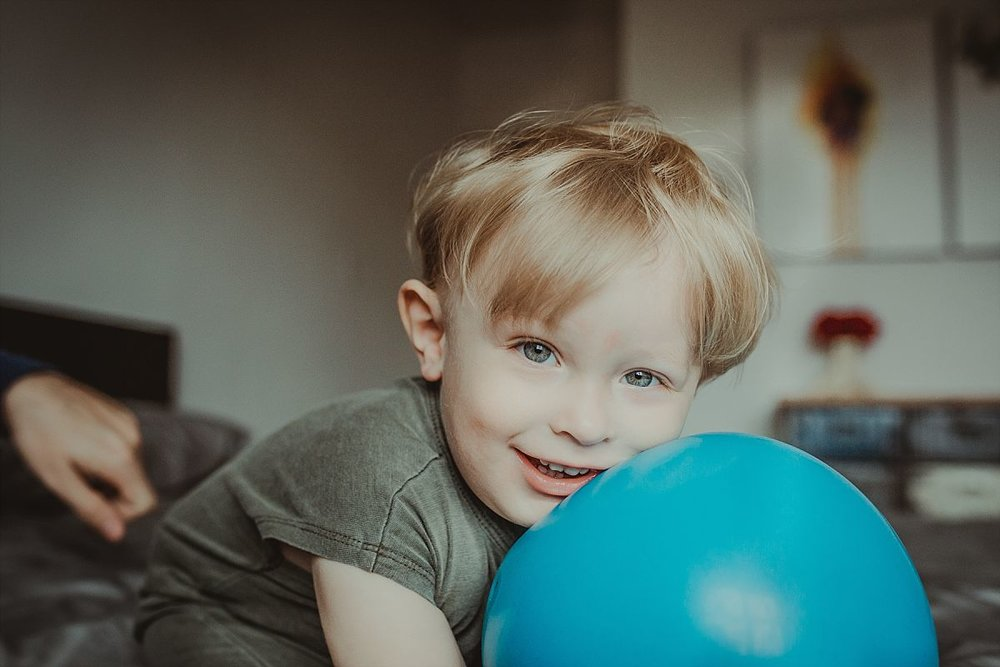 nyc family and newborn photographer boy leans on big blue ball with big smile