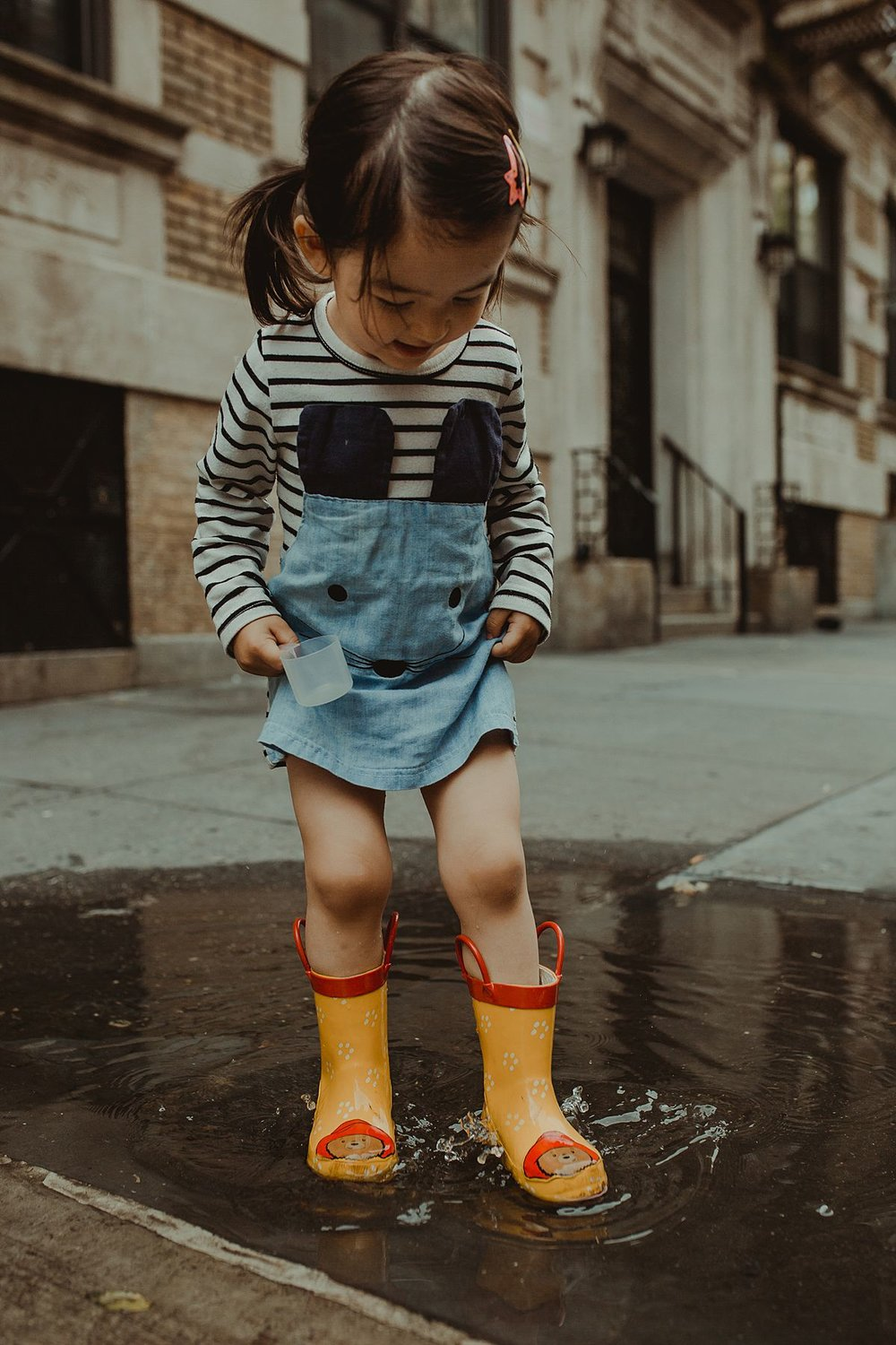 daughter splashing in puddle in yellow paddington bear rainboots. krystil mcdowall photography captures fun childhood moments