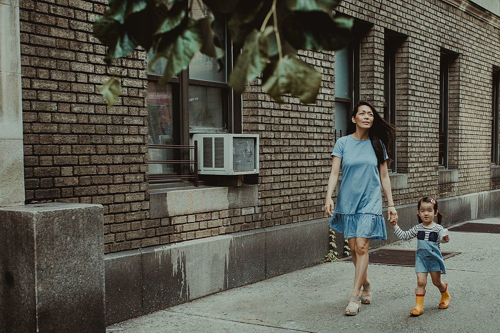 mom and daughter hold hands walking along nyc sidewalk in blue dresses. nyc family and newborn photographer krystil mcdowall capturing beautiful family moments to be treasured for a lifetime