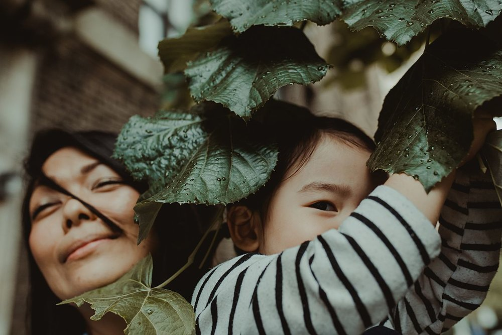 mom and daughter playing among tree leaves on nyc sidewalk. Krystil mcdowall photography capturing silly moments of your family