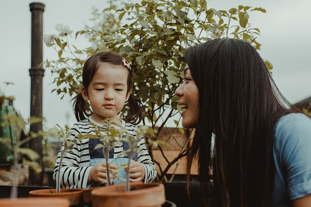mom and daughter play with potplants and daughter is curious about plants and asks mom questions. capturing your fun family moments is nyc family and newborn photographer krystil mcdowall photography