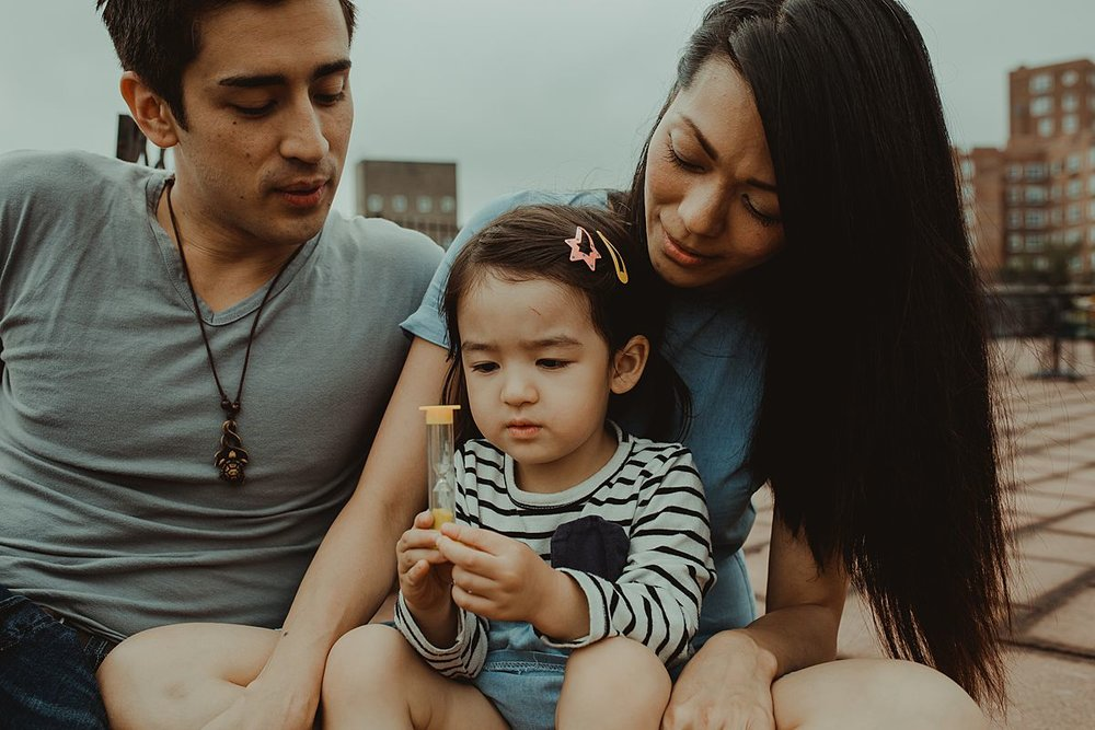 daughter plays with yellow hourglass while sitting on mom's lap during documentary nyc family photo shoot